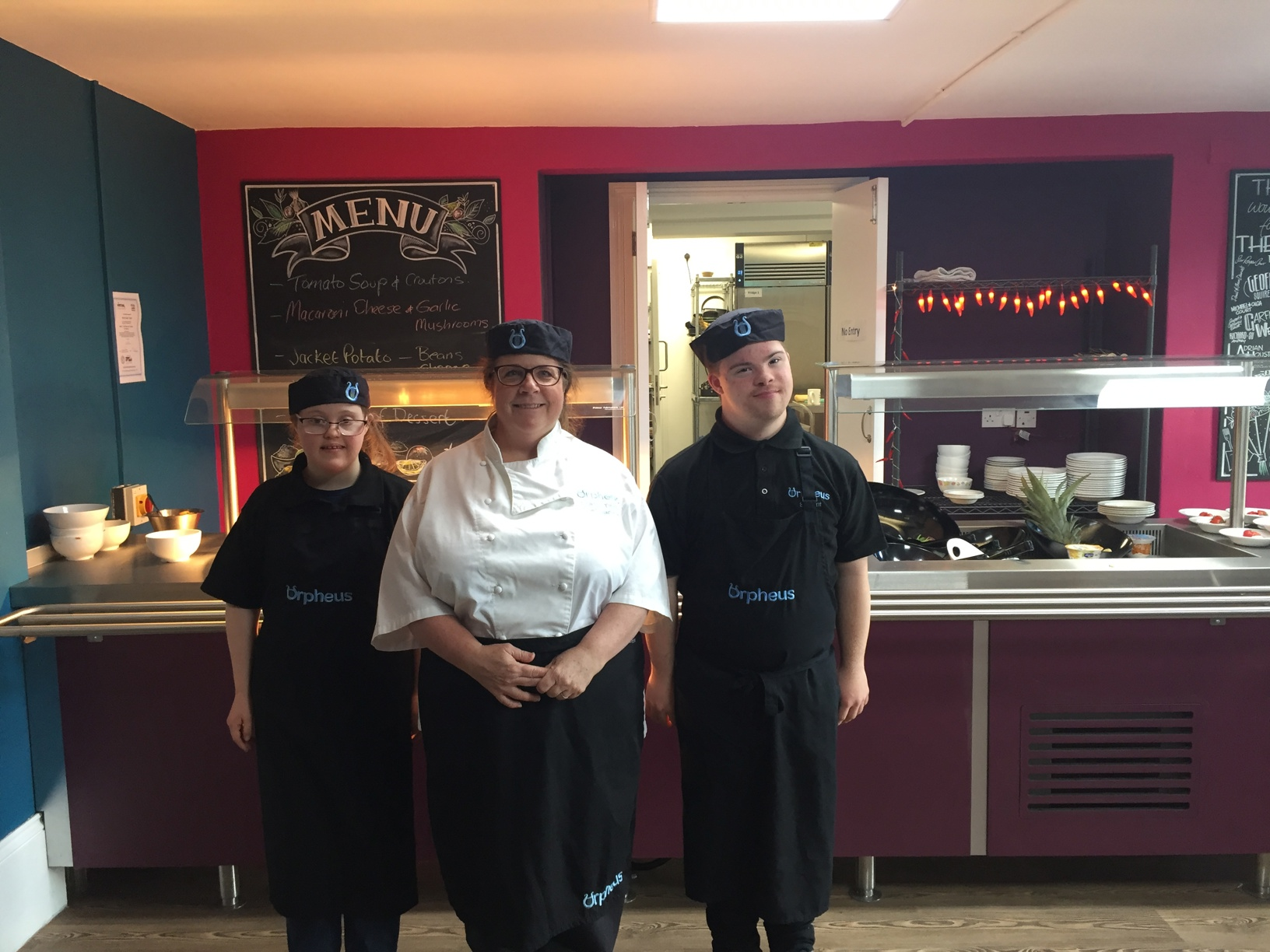 Young woman and man aged between 20 and 25 with learning disabilities. Posing for a photograph working in The Orpheus Centre canteen with head chef.