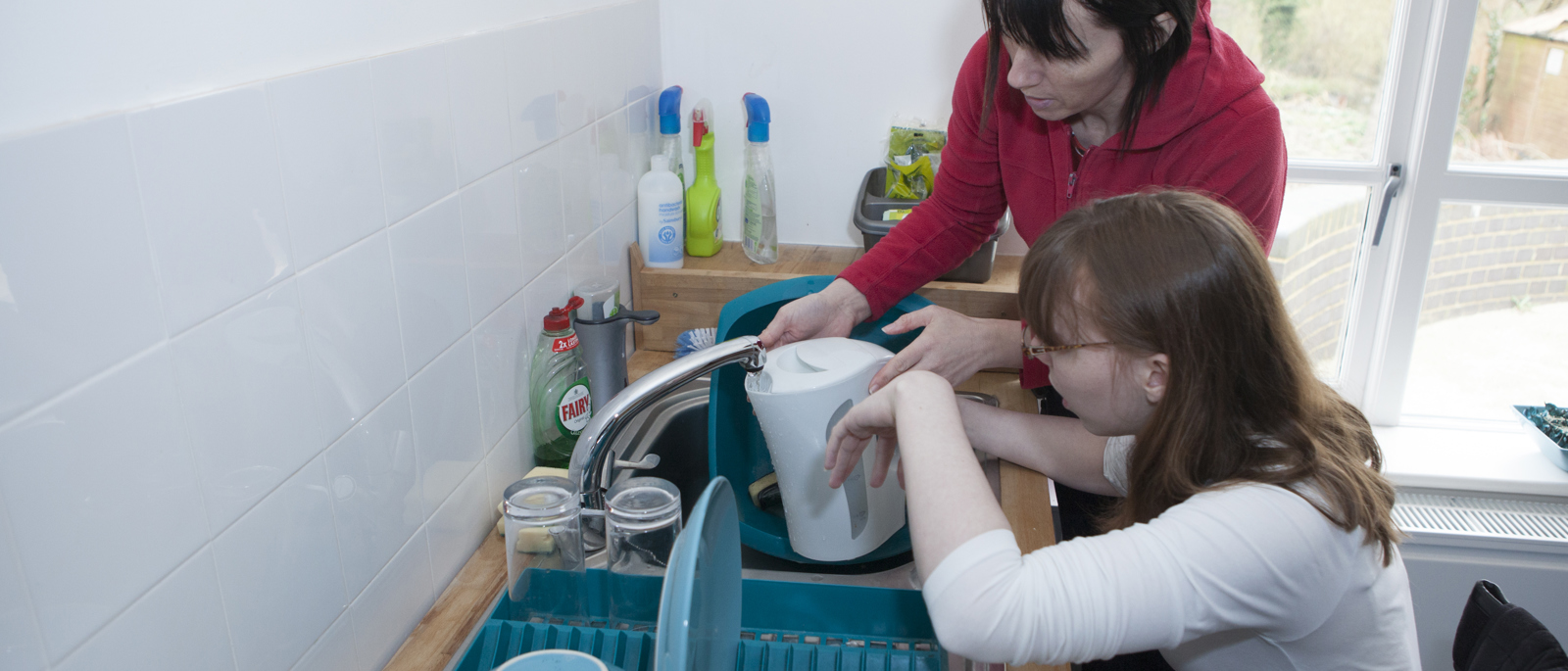 Student being supported when cooking by a member of the support team