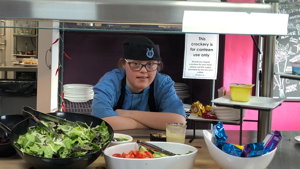 Young woman aged between 20 and 25 with learning disabilities. Posing for a photograph of her working in The Orpheus Centre canteen.