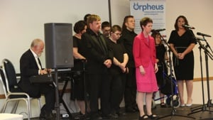 Group of disabled performers aged 18 to 25 enjoying singing on a stage with Sir Richard Stilgoe